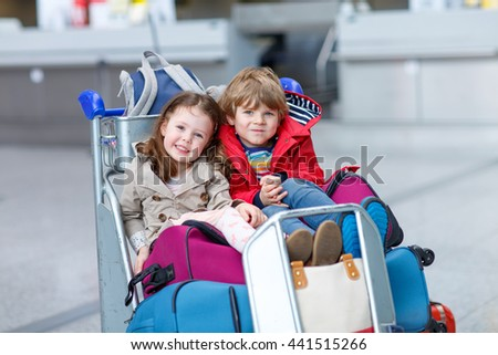 two little kids on international airport, sitting on suitcases. Brother and sister having fun and wating for flight