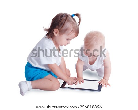 Two little kids playing with tablet PC computer, isolated on white background. Baby hand pointing on  touch screen. - stock photo