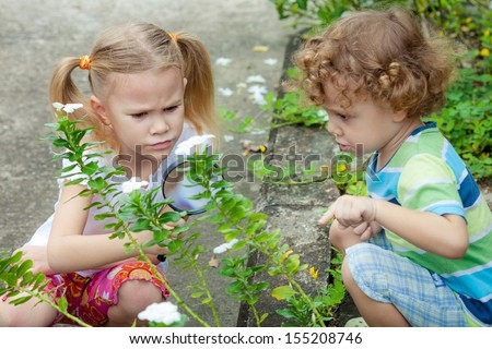 Two little kids with magnifying glass outdoors in the day time - stock photo