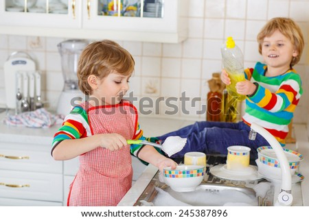 Two little lovely and funny kid boys washing dishes in domestic kitchen. Children having fun with helping with housework. Indoors, siblings in colorful clothes. Selective focus