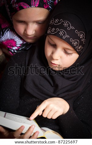 Two little muslim girls reading Holy Book Koran - stock photo