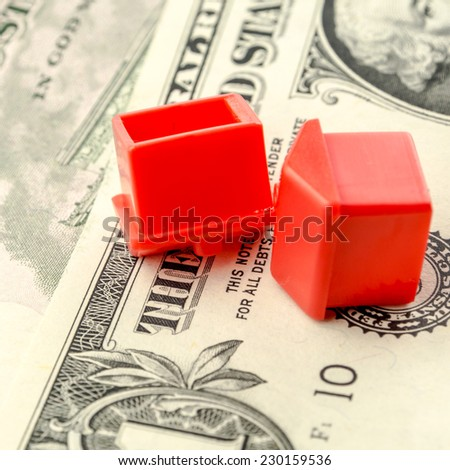 two little red houses made of plastic are laying on their roofs on dollar banknotes, business concept - stock photo