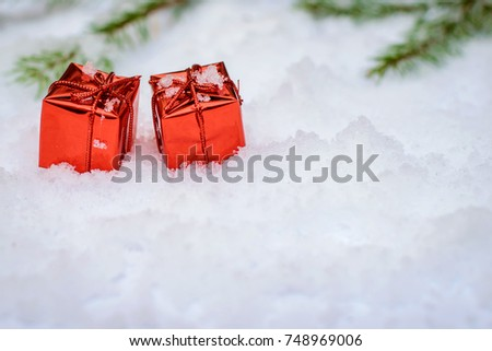 Two little red shiny boxes with Christmas gifts on the snow in winter