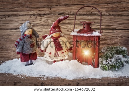 Two little santa decoration and burning lantern on wooden background - stock photo