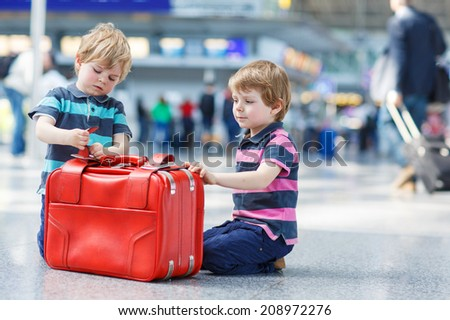 Two little sibling boys having fun and going on vacations trip with suitcase at international airport, indoors. - stock photo