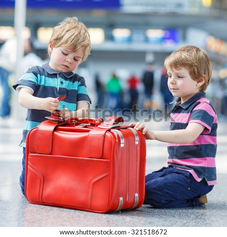Two little sibling boys having fun and going on vacations trip with suitcase at international airport, indoors.