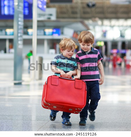 Two little sibling boys having fun and going on vacations trip with suitcase at intrernational airport, indoors. Kids and friends holding red suitcase and walking to the gate. - stock photo