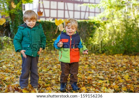 Two little sibling boys having fun with yellow foliage in autumn park