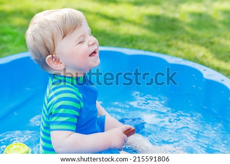 Two little sibling boys splashing with water in summer garden on sunny day, outdoors.