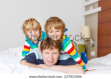 Two little sibling kid boys and their dad having fun in bed after sleeping at home, indoor. Brothers smiling at the camera. - stock photo