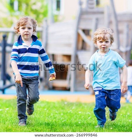 Two little sibling kid boys playing together on a playground, outdoors in summer. - stock photo