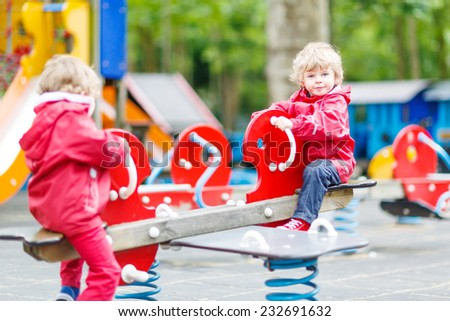 Two little sibling kid boys playing together on a playground, outdoors in summer. on a rainy day, selective focus on one boy - stock photo