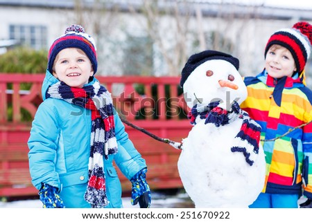 Two little siblings boys making a snowman, playing and having fun with snow, outdoors  on cold day. Active outoors leisure with children in winter. Selective focus - stock photo