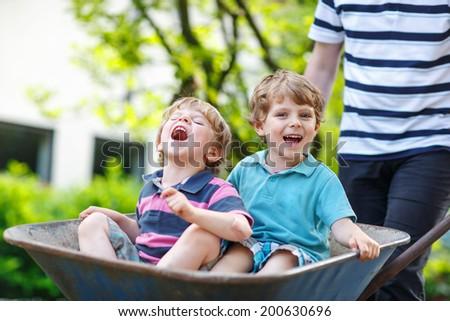 Two little siblings having fun in a wheelbarrow pushing by father in summer garden - stock photo
