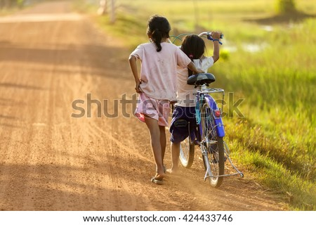 Two little sisters are walking on a dirty road at sunset in Cambodia.
