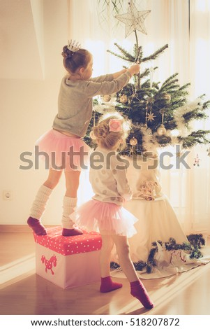two little sisters decorating christmas tree