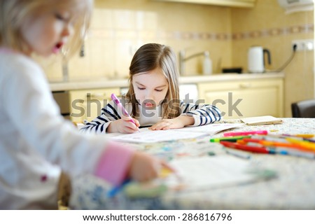 Two little sisters drawing and learning together at home - stock photo