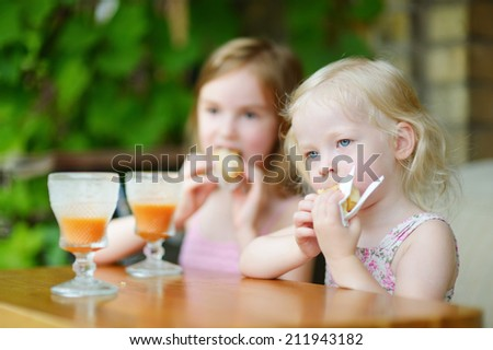 Two little sisters drinking orange juice and eating pastries in an outdoor cafe on warm and sunny summer day - stock photo