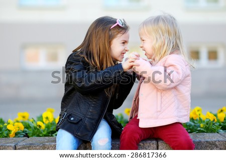Two little sisters fighting outdoors - stock photo