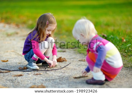 Two little sisters having fun in beautiful autumn park - stock photo