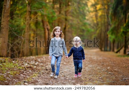 Two little sisters having fun in the woods on beautiful spring day - stock photo