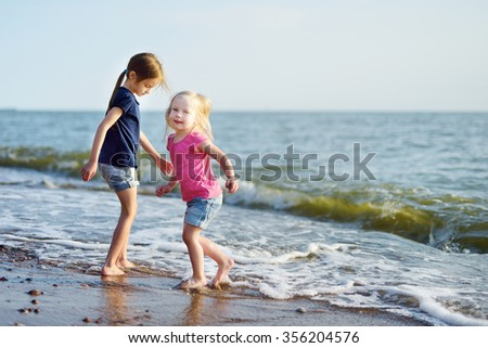 Two little sisters having fun on a sandy beach on warm and sunny summer day - stock photo