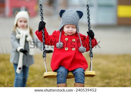 Two little sisters having fun on a swing on early spring - stock photo