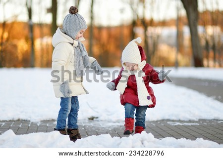 Two little sisters having fun on white and snowy winter day - stock photo