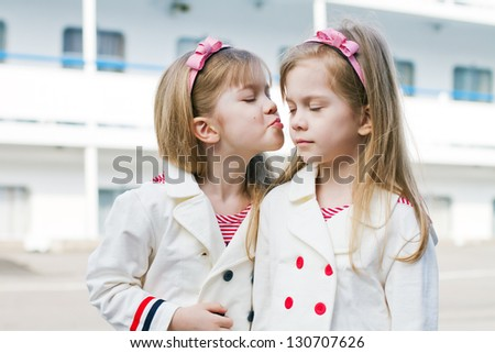 two little sisters in clothes in a nautical theme and a ship in - stock photo