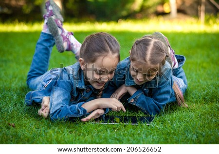 Two little sisters lying on green grass and playing on tablet