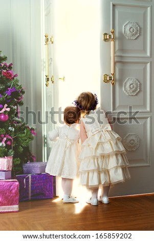 Two little sisters opening the doors and looking out something magic near the Christmas tree - stock photo