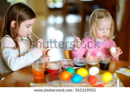 Two little sisters painting colorful Easter eggs at home
