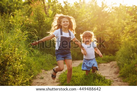 Two little sisters run on the road in park on a sunny summer day. Family time. Cute babies. Soft focus - stock photo
