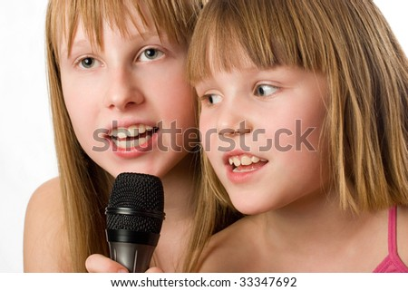Two little sisters singing in microphone. Isolated - stock photo