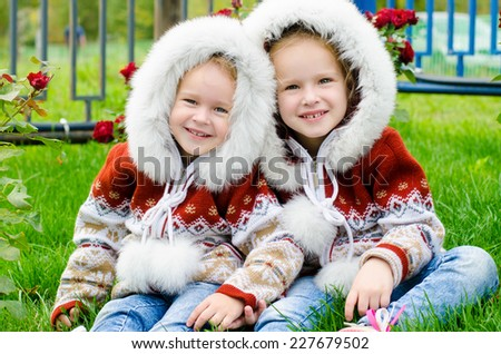 Two little sisters sitting, cuddling next to a bed of roses - stock photo