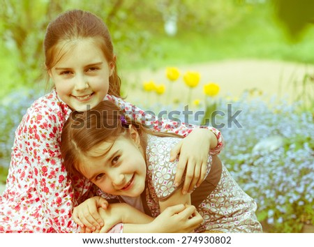 Two little sisters spending time together outdoor - stock photo