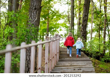 Two little sisters walking up stairs in summer park on beautiful sunny day - stock photo