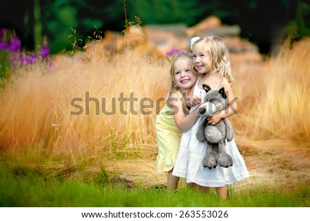 two little smiling blond girls in the dresses are standing and hugging in the field and one of the girls is holding her toy wolf in her hands - stock photo