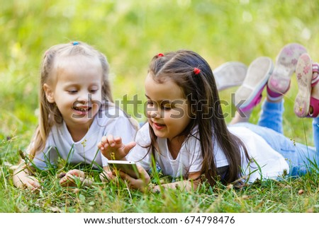 Two little smiling girls lying on the grass in the park. play in the mobile