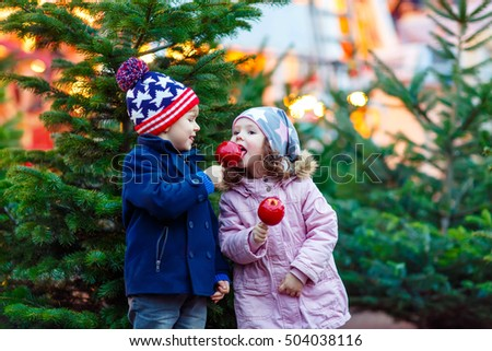 Two little smiling siblings, kids eating crystalized sugared apple on German Christmas market. Happy children, twins in winter clothes with lights on background. Family, tradition, holiday concept