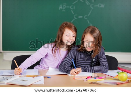 Two little students sitting and studying at school class