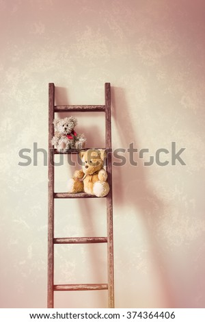 Two little teddy bears sitting on the rungs of a wooden ladder - stock photo