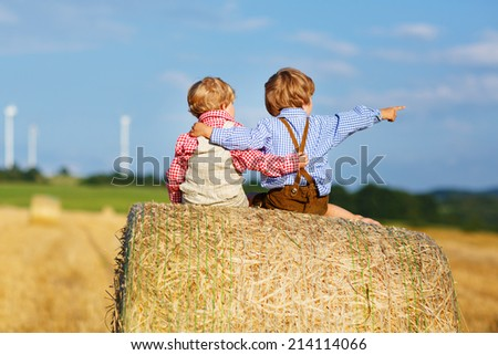 Two little twin boys sitting on hay stack or bale and speaking on yellow wheat field in summer - stock photo