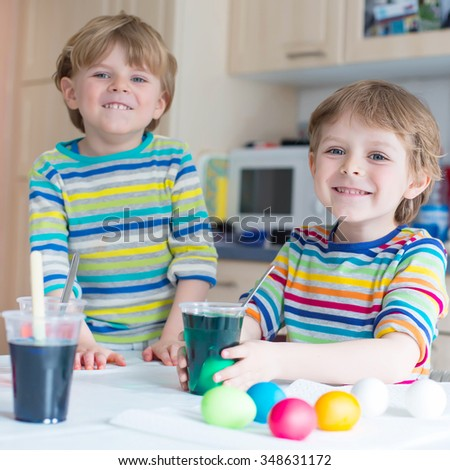 Two little twins boys coloring eggs for Easter holiday in domestic kitchen, indoors. Children having fun and celebrating feast.