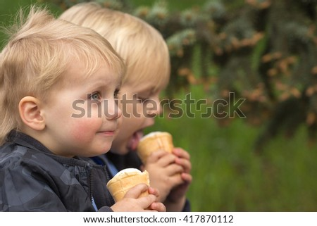 Two little twins boys eating ice cream outdoors - stock photo
