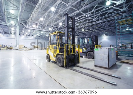 Two loaders in modern storehouse