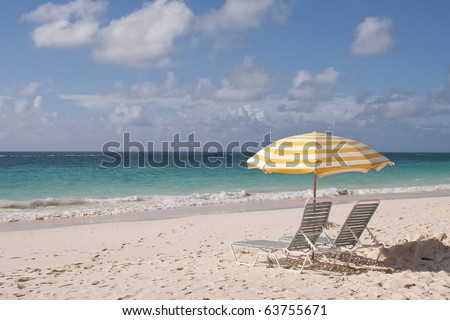 Two Lounge Chairs, and umbrella, beautiful pink sand beach, and crystal clear water on a beautiful sunny day. - stock photo