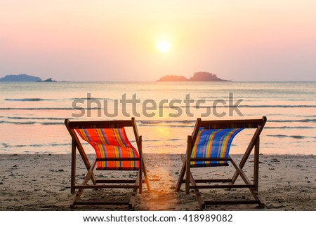Two lounge chairs on sunset beach.