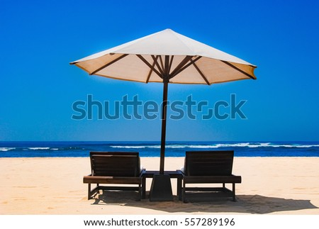 Two lounge chairs under an umbrella, standing in the sand on the beach of Nusa Duo.