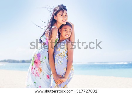 two lovely asian sisters on a beach - stock photo